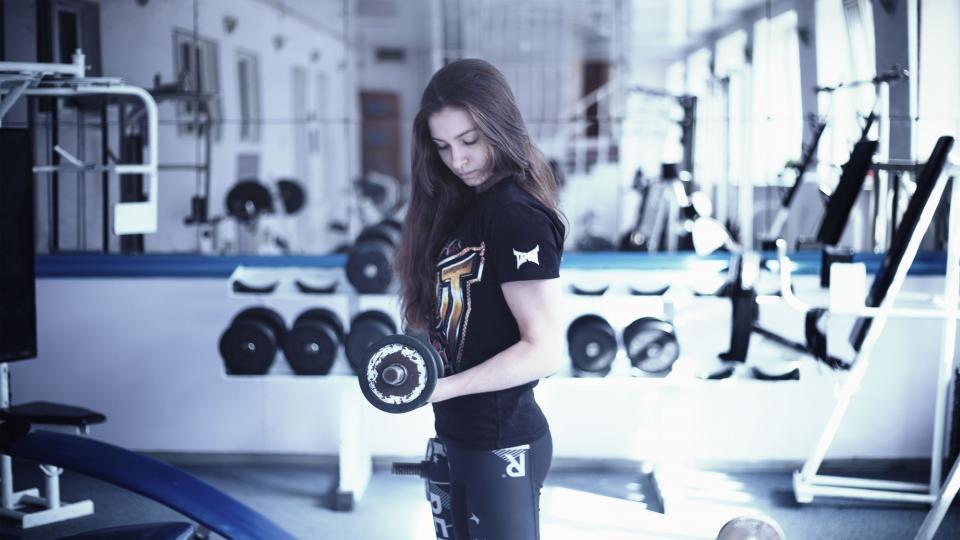 Girl Lifting Weights At Gym